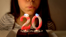 Girl Blowing Out A 20th Birthd...