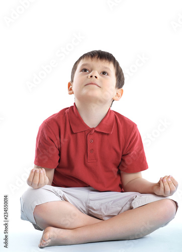 little boy is sitting in the Lotus position.isolated on white