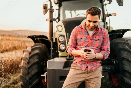 Portrait of smiling farmer using smartphone and tractor at harvesting Fototapete