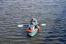 Man Fishing In A Kayak On A Peaceful Lake