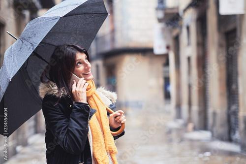 Fototapeta Mujer joven hablando por teléfono en un día de invierno lluvioso