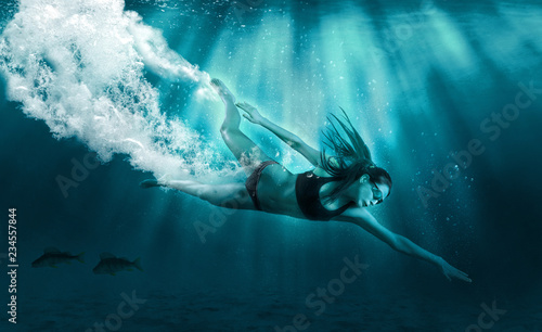 Athletic girl diver alone in the depths of the ocean