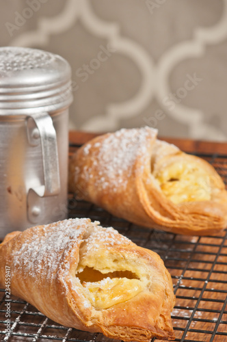 Fotografie, Obraz  Front view, close up of two freshly baked cheese danish pasteries with powdered