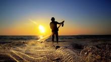 Fishermen Working Repairing Fishing Nets On Ocean Coast At Sunset, Cinematic Shot