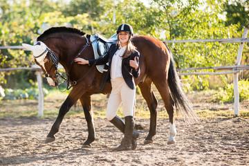 Girl equestrian rider stands near the horse. Horse farm. Horse raises his leg. Horse theme