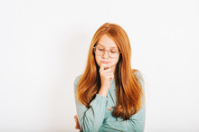 Studio Shot Of Young Preteen Red-haired Girl Against White Background, Holding Hand On The Chin, Looking Down