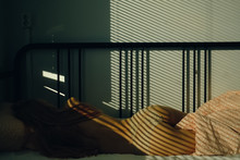 Woman Sleeps In Bed At The Morning With The Bright Window Lights On Her Body