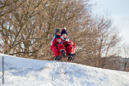 Poster Glisse hiver Two boys at the sledge on the top of snowy hill waiting for ridi