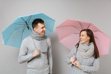 Couple Girl Guy In Gray Sweaters Scarves Together Under Umbrella Isolated On Grey Wall Background, Studio Portrait. Healthy Lifestyle Ill Sick Disease Treatment Cold Season Concept. Mock Up Copy Space