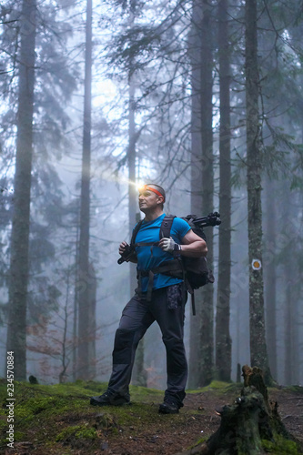 Obraz Man with headlamp and backpack in the forest - fototapety do salonu