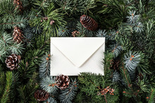 Christmas Letter Envelope On Fir Branches Background With Pine Cones. Xmas And New Year Theme. Flat Lay, Top View