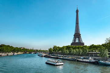Seine in Paris with Eiffel tower and tourist boat in beautiful summer day