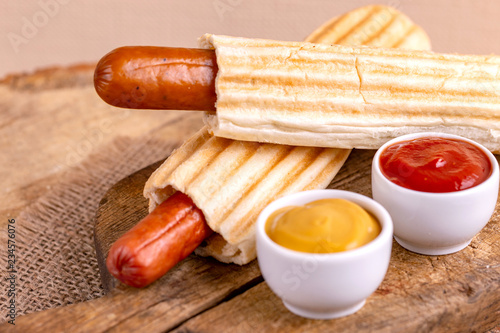 Obraz Two tasty grilled french hot dog with mustard and ketchup - fototapety do salonu