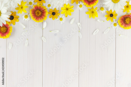 Foto auf Leinwand Blumen White daisies and garden flowers on a white wooden table. The flowers are arranged in the upper part, the empty space left below.