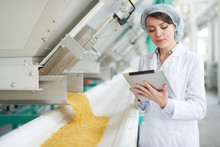 Waist Up Portrait Of  Young Woman Standing By Machines And Using Digital Tablet While Inspecting Macaroni Production At Food Factory , Copy Space