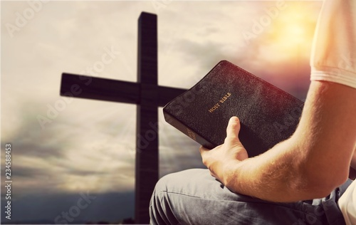 Photo  Man reading old Bible book on background