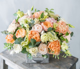 Bouquet of fresh spring flowers on gray wall background. Floral arrangement in vintage metal vase. flower shop, florist work