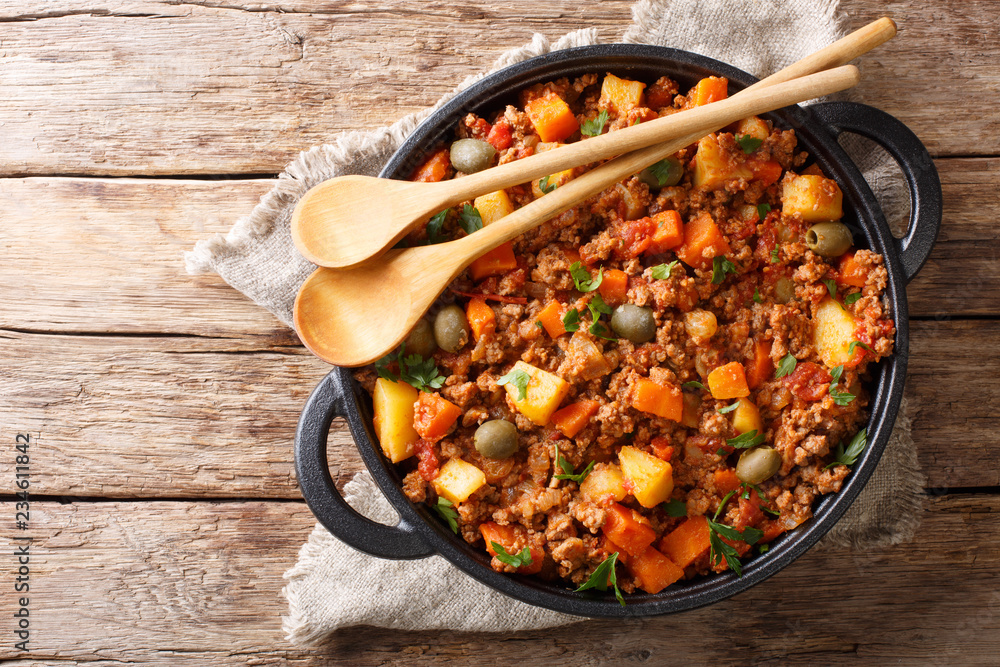 Fototapeta Delicious Picadillo cooked from ground beef with vegetables, raisins and spices close-up in a frying pan. horizontal top view