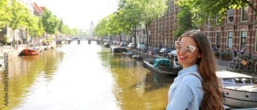Fototapeta premium Portret dziewczyny podróżnik z okulary i plecak korzystających z miasta Amsterdam. Panoramiczny widok banner młodej kobiety, patrząc do kamery na kanale Amsterdam, Holandia, Europa.