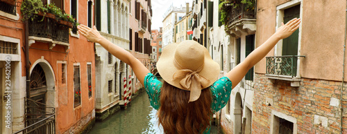 fototapeta na ścianę Europe travel vacation fun summer woman with arms up and hat happy in Venice, Italy. Panoramic banner view of carefree girl tourist in European destination wearing green fashion dress.