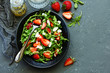Fresh salad with arugula, strawberries and almonds. Selective focus.