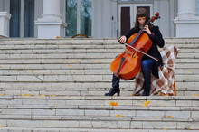 Young Woman Playing Cello On The Steps Of Marble Staircase Of An Ancient House