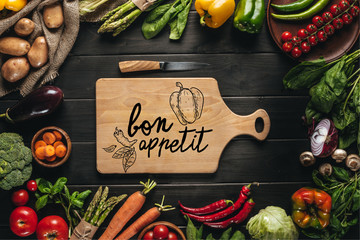 Fototapeta Do restauracji top view of cutting board with knife and organic fresh vegetables around on wooden tabletop, bon appetit lettering