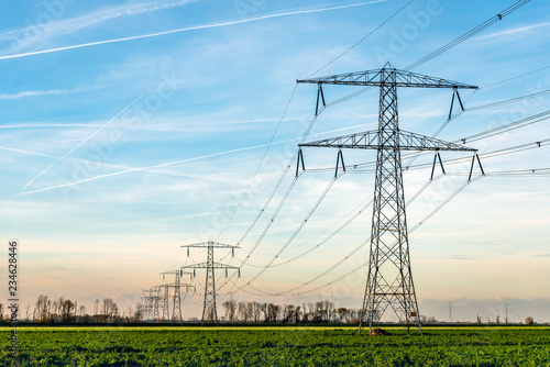 Valokuva  High voltage towers with thick hanging power cables in a rural landscape in the