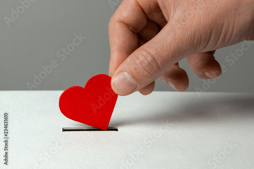 Foto Man's hand places heart in the donation slot