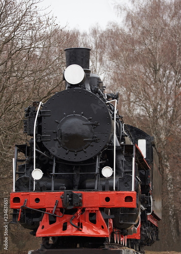 Fototapeta Front  view of old classic black  steam locomotive with red decoration on railroad track obraz na płótnie