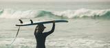 kobieta surfer z deską surfingową w wodzie patrząc na nadchodzące fale - 234637075