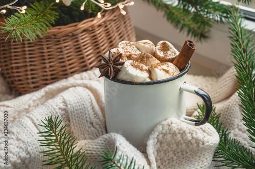 Winter warming mug of chocolate with marshmallow on windowsill with Christmas tree decor and garland.