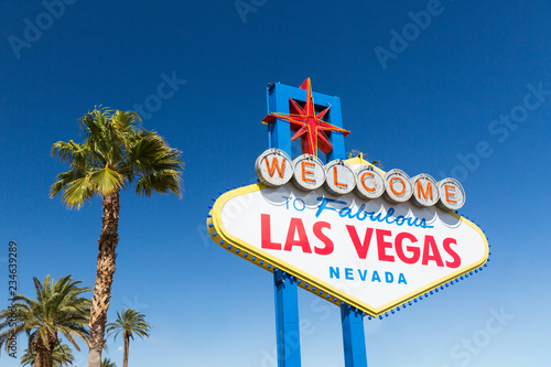 Photo  landmarks concept - welcome to fabulous las vegas sign and palm trees over blue