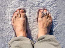 Men's Bare Feet In The Snow In A Sunny Day.