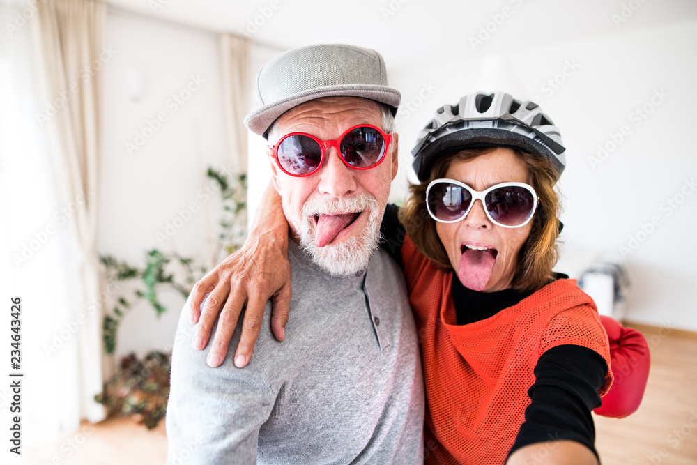 Fototapety, obrazy: A senior couple with sunglasses having fun at home.