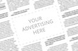 canvas print picture - Close up of a copy space with wrtitten words Your Advertising Here on a blurred background of a newspaper. Business concept. Adding ad into paper page. Mockup of a newspaper advertisement column.