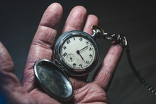 Old Man Holds In His Hand A Retro Pocket Watch On A Chain, The Concept Of A Bygone Time And Old Age