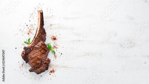 Foto op Aluminium Steakhouse Steak on the bone. tomahawk steak On a white wooden background. Top view. Free copy space.