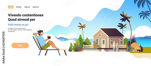 young man wear digital glasses sitting sun lounger virtual reality vision villa house tropical beach summer vacation concept flat copy space