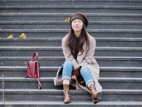 Fotografía  Portrait of beautiful young woman thinking sitting on wooden steps in a park outdoors background late autumn, smiling with eyes closed, with red bag beside her