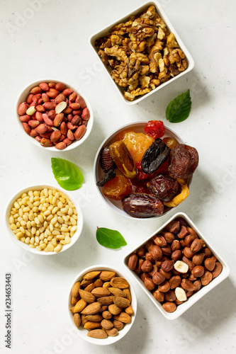 Various Nuts in a ceramic bowl and Dried Fruits on a light stone table. The Concept of a Healthy Dessert. Top view flat lay background.