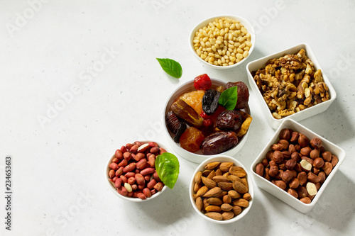 Various Nuts in a ceramic bowl and Dried Fruits on a light stone table. The Concept of a Healthy Dessert. Copy space.