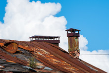 Old Rusty Metal Roof With Brick Chimney