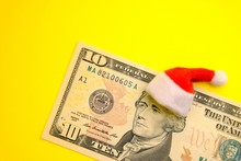 President Hamilton In A Red Santa Claus Hat On A Ten US Dollar Bill Against A Bright Yellow Background. The Concept Of The Cost Of Christmas Holidays, Debt, Profits Or Discounts For The New Year.