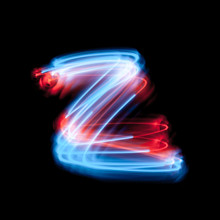 Letter Z Of The Alphabet Made From Neon Sign. The Blue Light Image, Long Exposure With Colored Fairy Lights, Against A Black Background