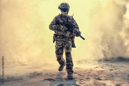 Fotografía  Army soldier in military camouflage uniform, helmet, with face hiding behind mask and glasses, running out from fire