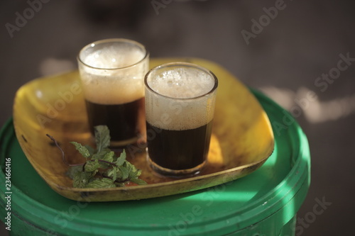 close up of traditional african tea - black strong green attaya in small glasses on a yellow plate, outdoors in the Gambia, Africa