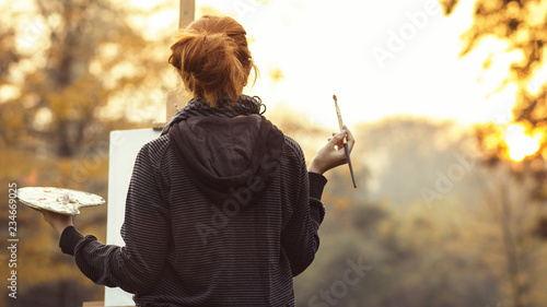 red-haired girl with painting a picture on an easel in nature, a young woman involved in creativity and enjoying beautiful landscape at sunset