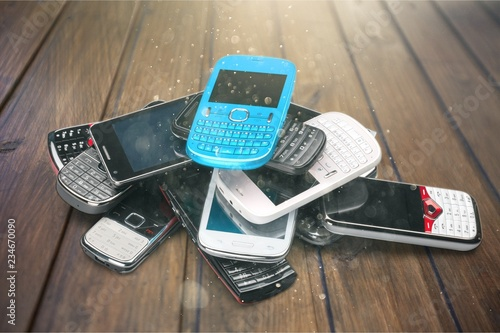 Pile of old smartphones on wooden background