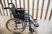 Empty Modern Wheelchair Near Brick Wall Indoors.